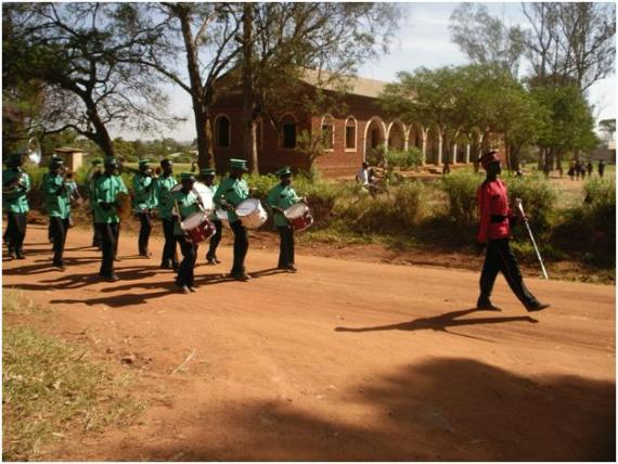 The procession for an Acholi wedding marching down the road