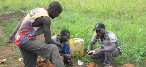 three workers cooking a bush rat
